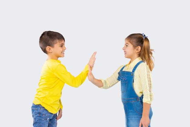 Nette kinder auf einem weißen hintergrund haben spaß und spielen lieblinge. das konzept der emotionen und des zeitaufwands von kindern.