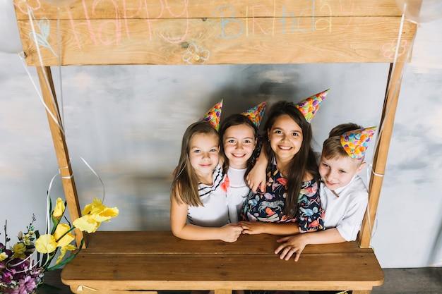 Nette kinder, die auf geburtstagsfeier umfassen