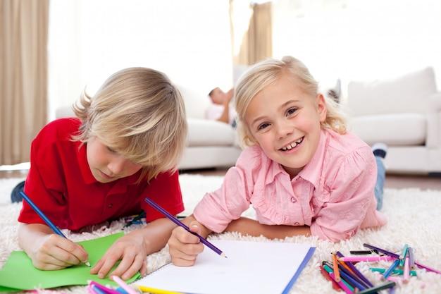 Nette kinder, die das lügen auf dem boden zeichnen