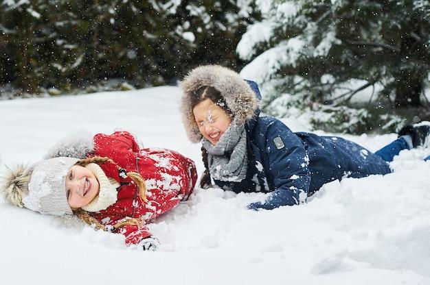 Nette kinder, die im schnee draußen nahe den weihnachtsbäumen spielen
