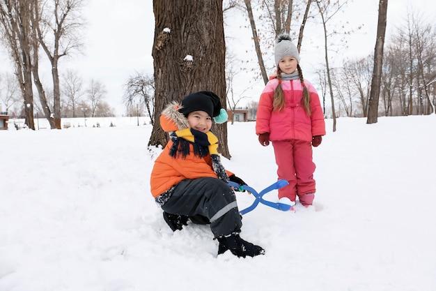 Nette kinder, die im schneebedeckten park in den winterferien spielen