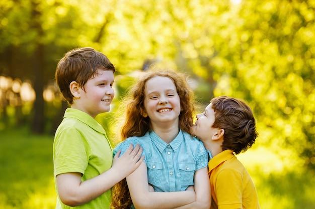 Nette kinder, die im sommerpark stillstehen. familie, glückliche kindheit konzept.