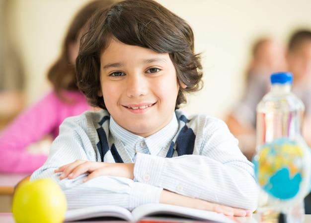 Nette kinder, die mit apfel und kugel auf schreibtisch im klassenzimmer sitzen