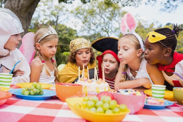Nette kinder, die zusammen auf der kerze während einer geburtstagsfeier durchbrennen