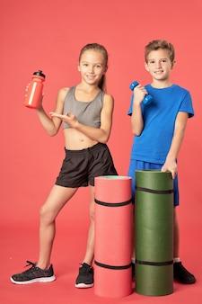 Nette kinder mit sportgeräten, die vor rotem hintergrund stehen