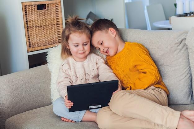 Nette kinder sprechen per videoanruf mit einem tablet. quarantäne. eine familie. zuhause. gemütlich. Premium Fotos