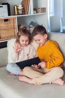 Nette kinder sprechen per videoanruf mit einem tablet. quarantäne. eine familie. zuhause. gemütlich.