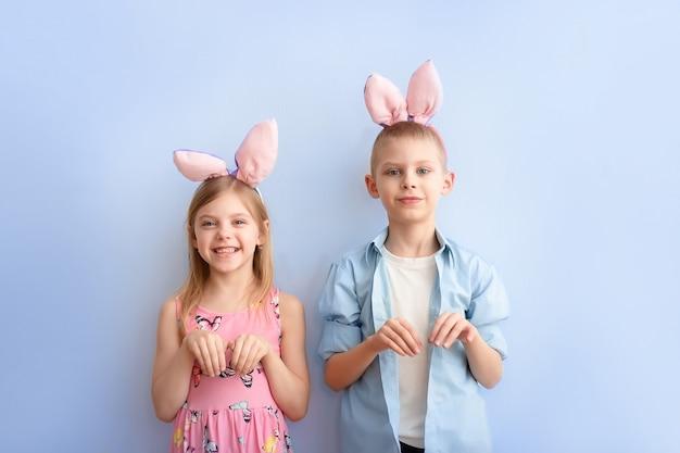 Nette kinder tragen hasenohren auf ihren köpfen und zeigen einen osterhasen am ostertag auf einer blauen wand