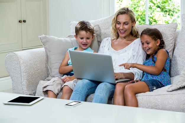 Nette kinder und mutter, die laptop auf sofa verwendet