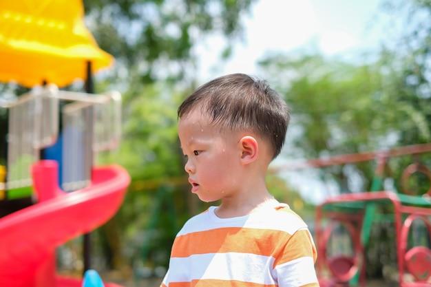 Nette kleine asiatische 2 - 3 jahre alte kleinkindjungenkind, die während des spielens des spaßes, trainieren im freien am spielplatz, hitzschlagkonzept schwitzen