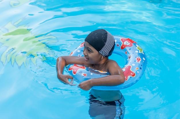 Nette kleine asiatische jungenschwimmen im pool