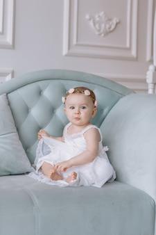 Nette kleine frau im weißen kleid und in den reifen der blumen auf dem kopf sitzt auf einer couch in einem klassischen stil und hat spaß zu hause.