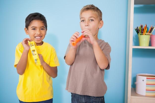 Nette kleine jungen, die musikinstrumente im klassenzimmer spielen