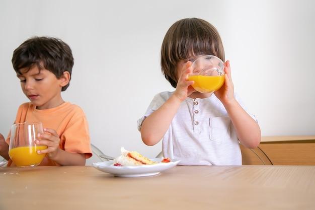 Nette kleine jungen, die saft trinken und kuchen mit sahne essen. zwei reizende kaukasische kinder, die am tisch im esszimmer sitzen und geburtstag feiern. kindheits-, feier- und feiertagskonzept