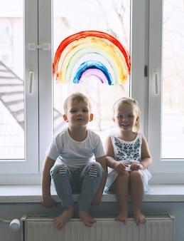 Nette kleine kinder auf dem hintergrund des malens des regenbogens auf dem fenster