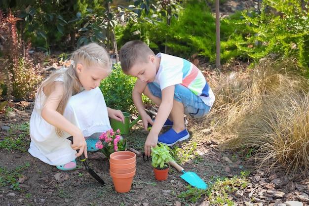 Nette kleine kinder, die blumen im garten pflanzen