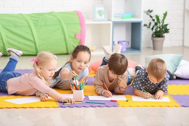 Nette kleine kinder, die im kindergarten zeichnen