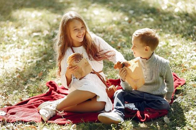 Nette kleine kinder, die in einem park mit brot sitzen