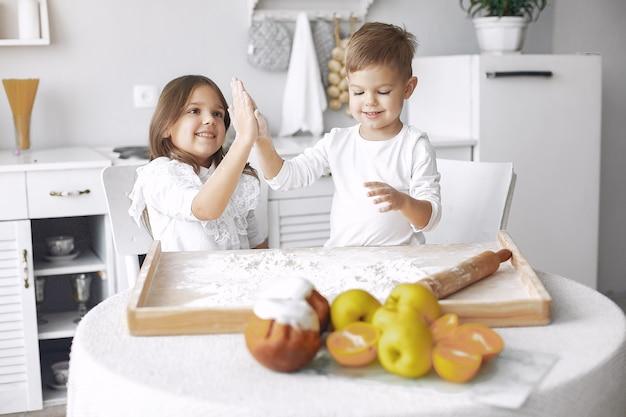 Nette kleine kinder, die in einer küche mit teig sitzen