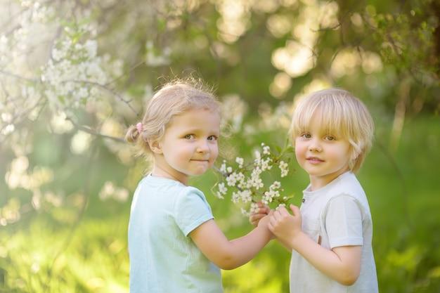 Nette kleine kinder, die zusammen in blühendem kirschgarten spielen.