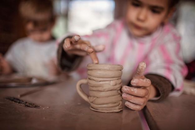 Nette kleine kinder, die zusammen mit modelliermasse in der töpferwerkstatt, im handwerk und in der tonkunst spielen