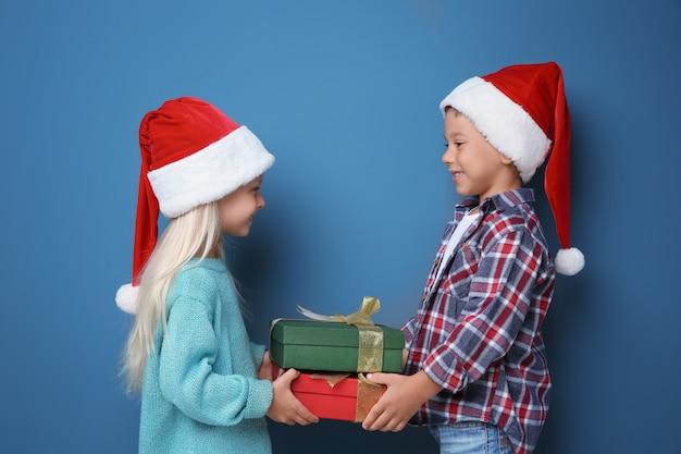 Nette kleine kinder mit weihnachtsgeschenken auf farbigem hintergrund