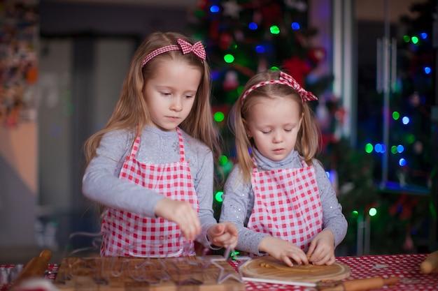 Nette kleine mädchen, die lebkuchenplätzchen für weihnachten zubereiten