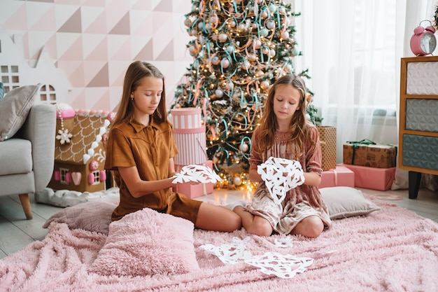 Nette kleine mädchen im wohnzimmer machen papierschneeflocken
