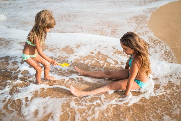 Nette kleine mädchen schwimmen im meer und sitzen am sandstrand und genießen den meeresschaum an einem sonnigen heißen sommertag.