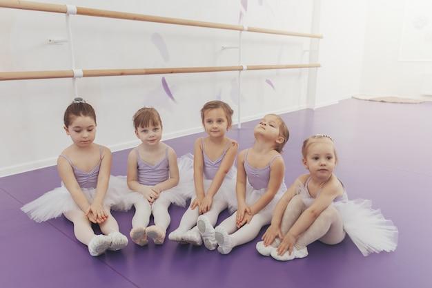 Nette kleine mädchen sitzen auf dem boden und ruhen sich nach ballettstunde im tanzstudio aus