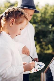 Nette kleinkinder, die in einem park malen