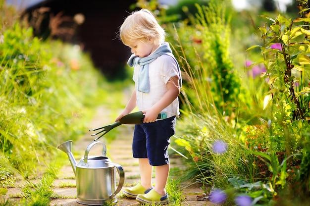 Nette kleinkindjungenbewässerungsanlagen im garten am sonnigen tag des sommers. kleines kind mit gartenwerkzeugen im inländischen garten