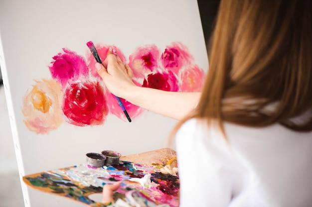 Nette künstlerin malt auf leinwand auf der staffelei.