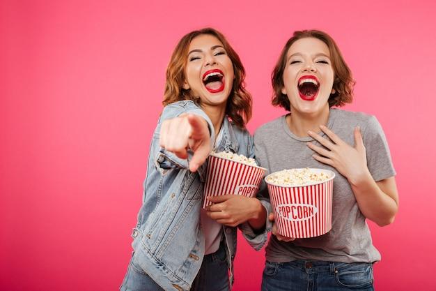 Nette lachende freundinnen, die das popcornuhr-filmzeigen essen.