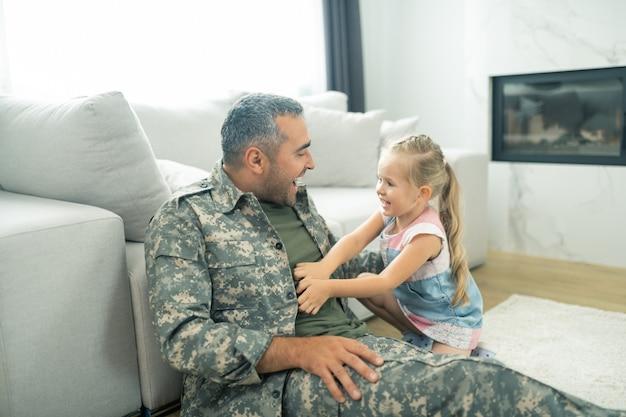 Nette lachende tochter. nette lachende tochter, die sich fröhlich fühlt, während sie mit papa in militäruniform spielt playing
