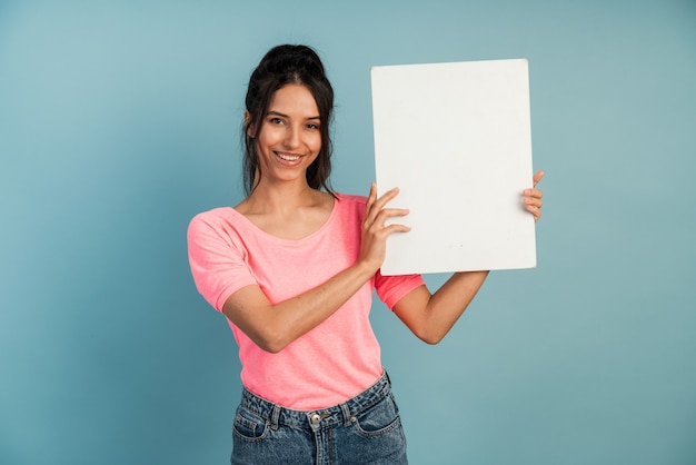 Nette, lächelnde brünette, die ein weißes blatt papier hält. mädchen posiert.