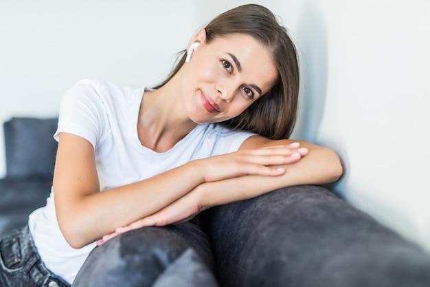 Nette lächelnde frau, die auf couch liegt, während über luftpods musik im hellen wohnzimmer hört
