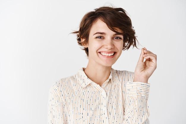 Nette lächelnde frau, die mit haaren spielt und konzept der hautpflege und weiblicher schönheit, weiße wand schaut