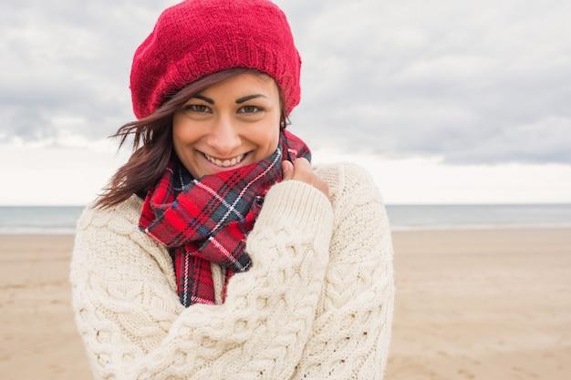 Nette lächelnde frau in der stilvollen warmen kleidung auf dem strand