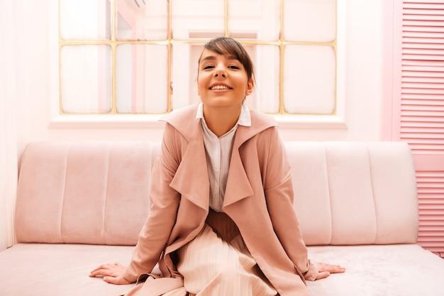 Nette lächelnde junge frau im mantel, der auf einem sofa sitzt