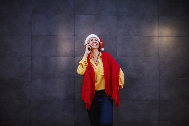 Nette lächelnde kaukasische blonde ältere frau mit kurzen haaren, weihnachtsmütze auf kopf und schal, die an die wand lehnen und auf smartphone sprechen.
