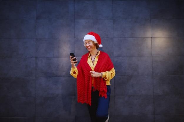 Nette lächelnde kaukasische blonde ältere frau mit kurzen haaren, weihnachtsmütze auf kopf und schal, die an die wand lehnen und nachricht auf smartphone tippen oder lesen.