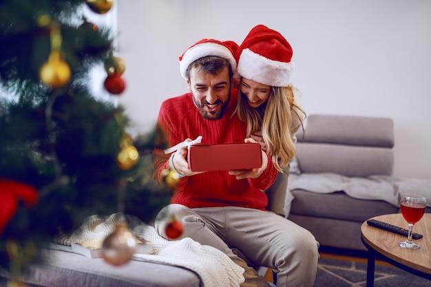 Nette lächelnde kaukasische blonde frau, die ihrem liebenden freund weihnachtsgeschenk gibt. beide haben weihnachtsmützen auf den köpfen. im vordergrund steht der tannenbaum. wohnzimmer interieur.