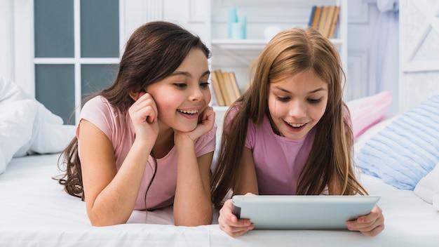 Nette lächelnde mädchen, die auf dem bett betrachtet digitale tablette liegen
