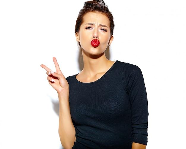 Nette lächelnde modefrau, die in der zufälligen schwarzen kleidung mit den roten lippen auf der weißen wand macht ein entengesicht und zeigt friedenszeichen verrückt geht