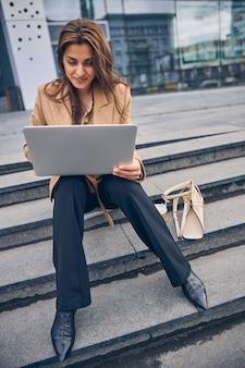 Nette lächelnde zufriedene moderne junge kaukasische geschäftsdame, die mit dem computer auf ihren knien sitzt