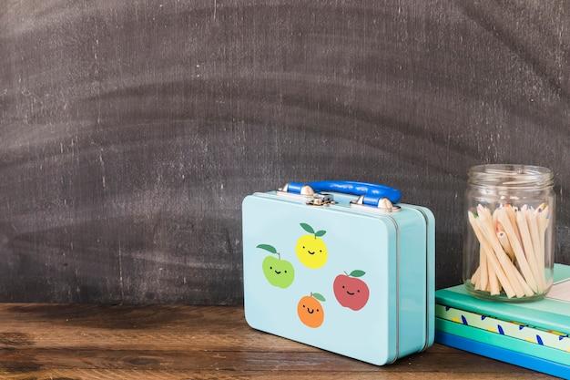 Nette lunchbox nahe bleistiften und notizblöcken