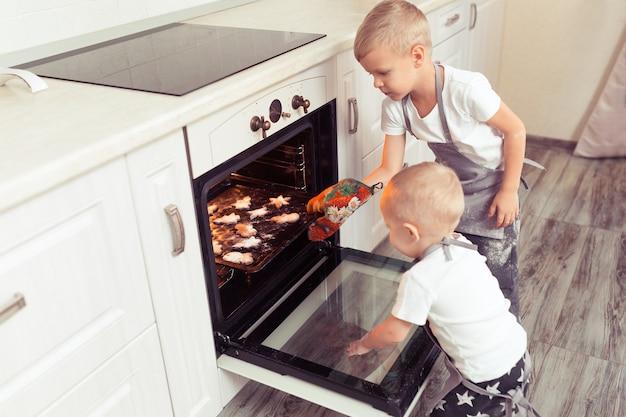 Nette lustige blonde kinderjungen, die lebkuchenplätzchen kochen und vorbereiten