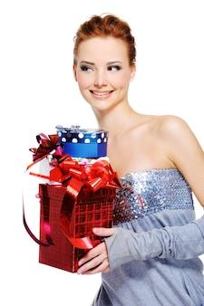 Nette lustige femlae, die die weihnachtsgeschenkkästen halten - lokalisiert auf weiß