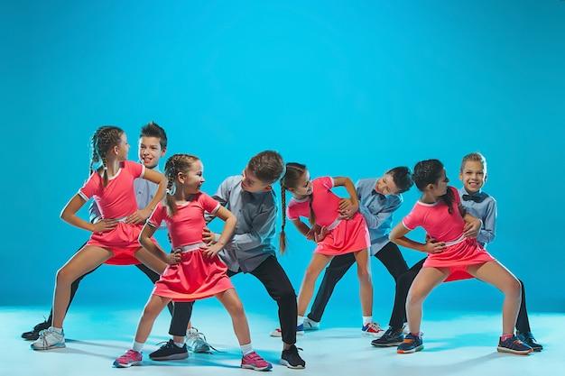 Nette lustige mädchen und jungen, die auf blau tanzen